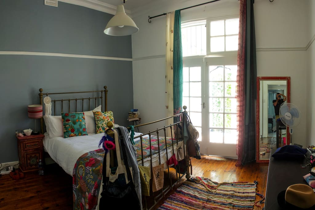 Large spacious main bedroom with high ceilings and wooden floors. Doors open onto balcony.
