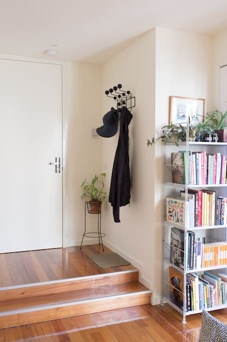 Apartment entrance with coat rack and bookshelf full of great books.