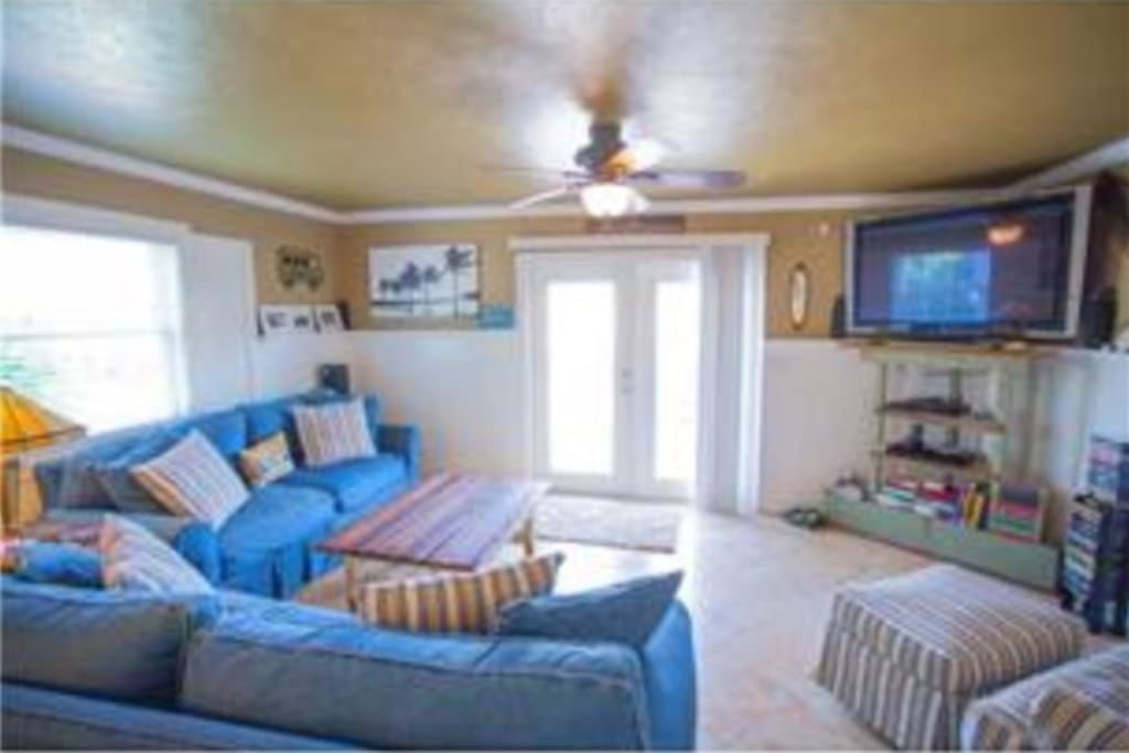 A large living room with a big screen TV and comfy furniture