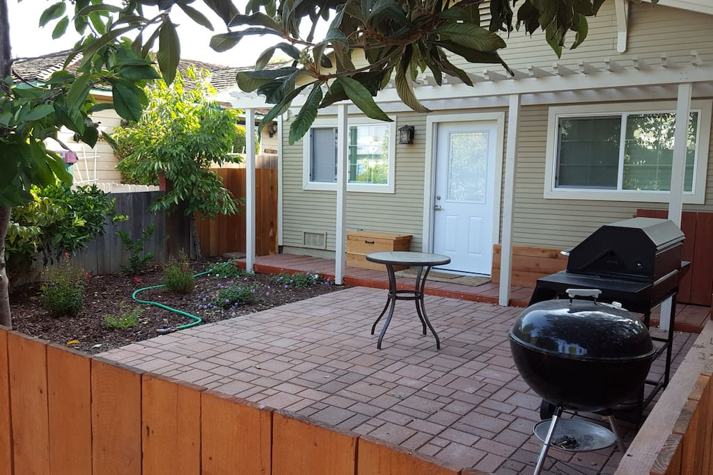 Outdoor, private yard with pergola and patio sitting area. Gas and charcoal grills available!
