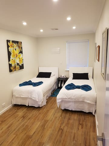 Bedroom 2: default arrangement of 2 x King Single beds. Fresh,  high quality linen and built-in mirrored robes