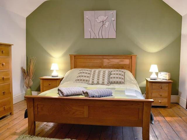 Double bedroom with solid oak furniture and wooden floors.