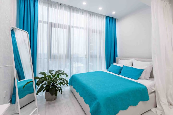 Двухспальная кровать с панорамным видом и с легкой воздушной перегородкой. На окнах гирлянды к Новому году, которые создают волшебную атмосферу✨