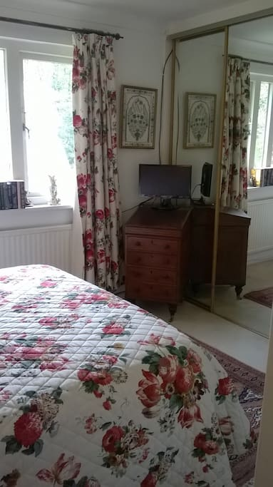 Bedroom 3 with en suite shower room.  A view of the TV, desk and mirrored wardrobes