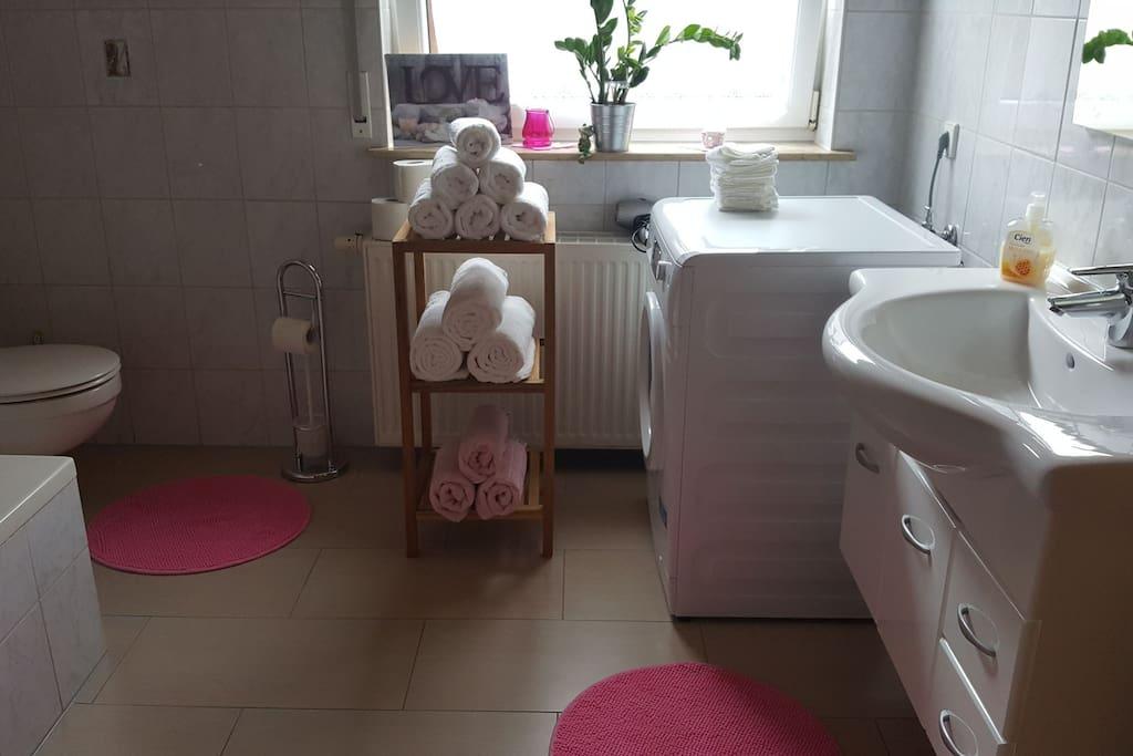 Badezimmer mit Badewanne , Waschmaschiene und Trockner vorhanden