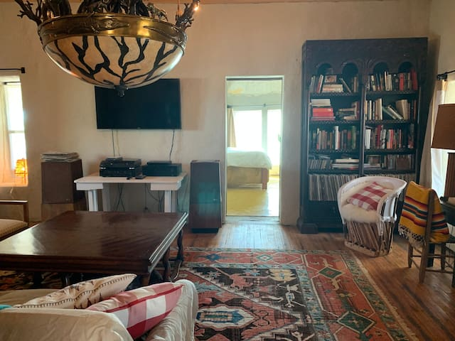 The living room view from the second bedroom. Many books and records to enjoy in the bookshelf. Stereo includes CD player, radio and turntable.