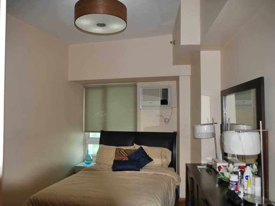Spacious bedroom with private bathroom, dresser, big closets and air conditioning unit.