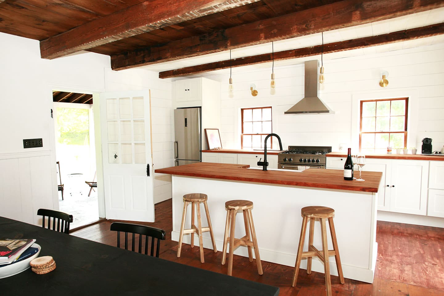 The kitchen door leads to a screened in porch with outdoor lounge chairs and a dining table.