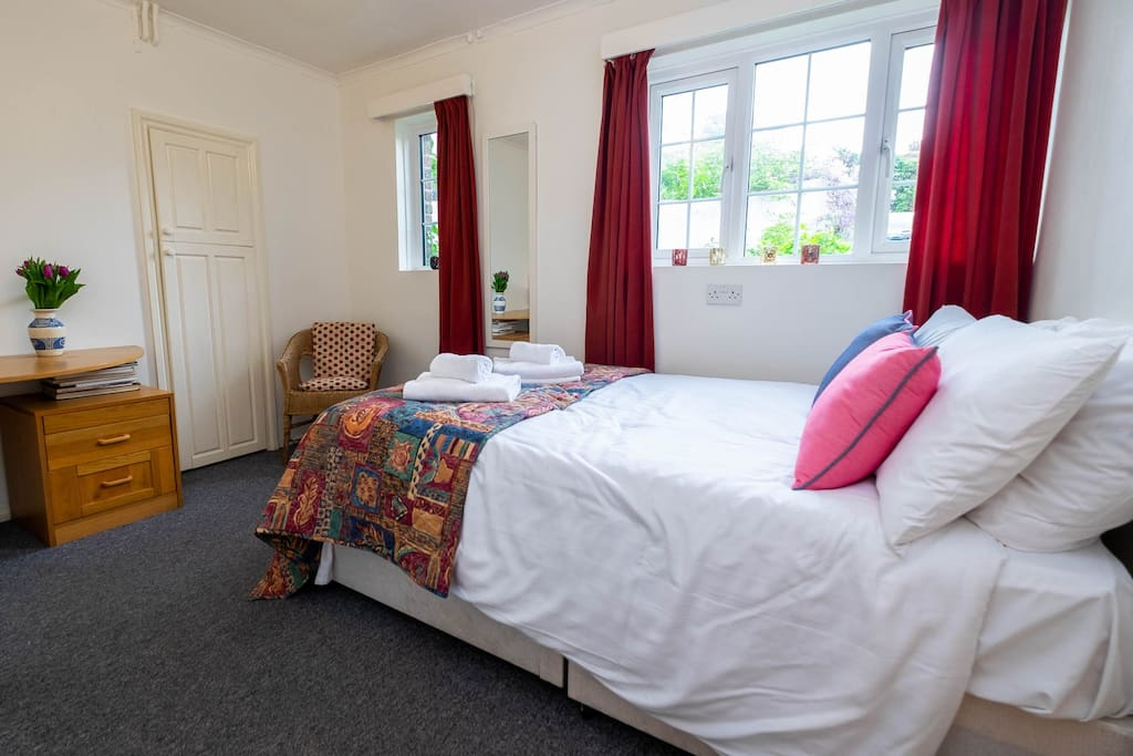 The comfortable double bed is made up with fresh white linen and towels