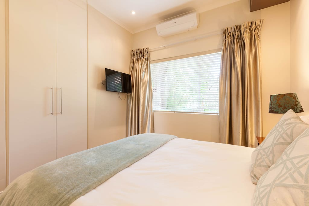 Air-conditioned bedroom with flat screen TV and lap-top size safe