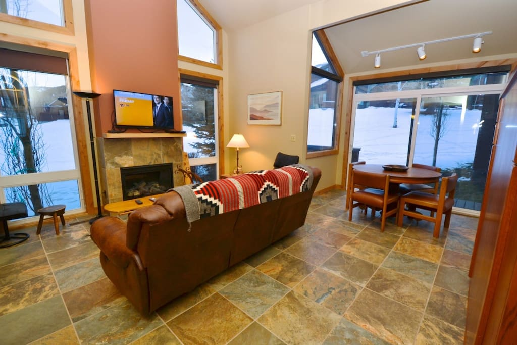 """Living room features a comfy leather sofa, 42"""" HDTV, full size murphy bed and floor to ceiling windows allowing natural light to fill the room."""