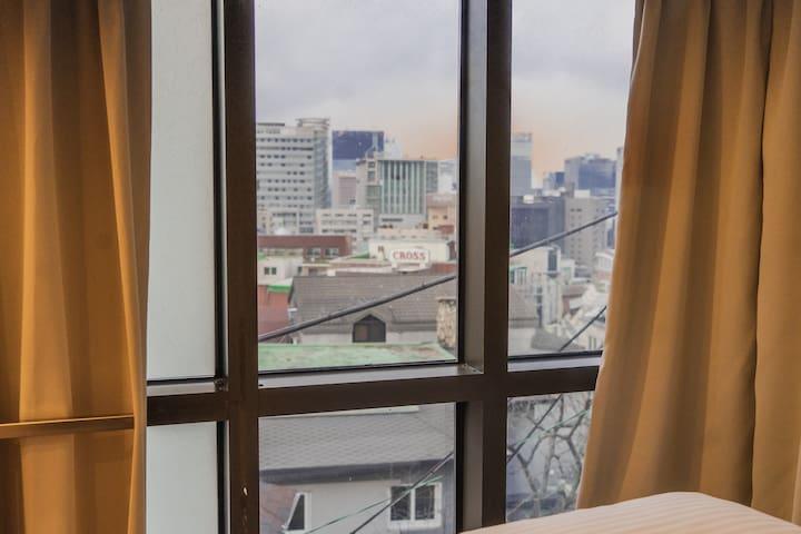 2층 침실입니다. 왼쪽에 보이는 1인 침대외에 멀리 보이는 쇼파에서 차를 마시며 명동을 야경을 바라보실 수 있습니다. 원하시면 쇼파를 펴서 침대를 더 넓게 사용하실 수 있습니다. 2nd floor bedroom. Aside from the single bed on the left photo, you can see the whole of myeong dong from the sofa next to the window.