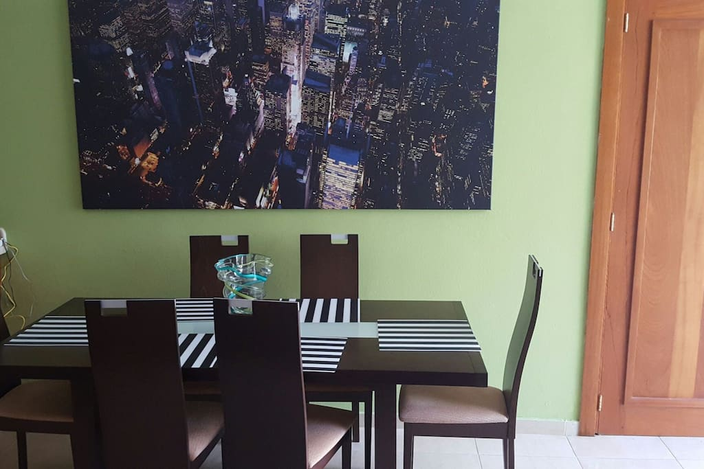 Dining area with modern table with portrait of a bird's eye view of NYC night sky.