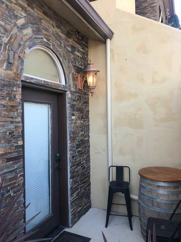 Beautifully rock framed studio entry door with wine barrel table and chars.