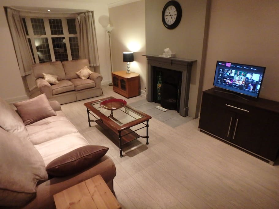 Large living room with smart TV, 2 & 3 seater sofas and original 1930s fire place