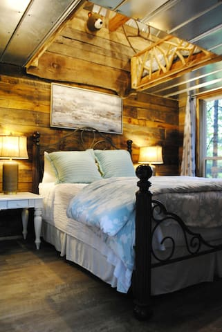 Queen bed on main level of Cedar Treehouse.  There is a pleasant cedar aroma (think cedar closet) in this bunkhouse due to the cedar used throughout the construction.