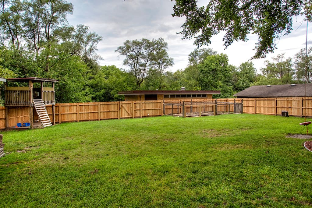 Expansive fenced back yard with treehouse and swing for the kids along with grill for cooking out