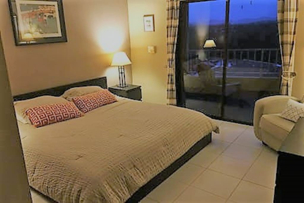 Master bedroom has a queen-size bed and sliding door with access to balcony.