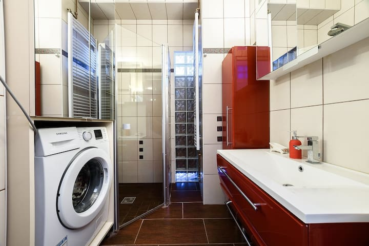 New bathroom with washing machine, sink and spacious shower
