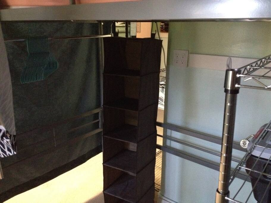 Storage for loft bed (under loft bed shown in previous picture). Includes clothes hanging rack, cloth shelves and metal wire shelves. Metal wire shelves have lockable black bin and storage bin available.