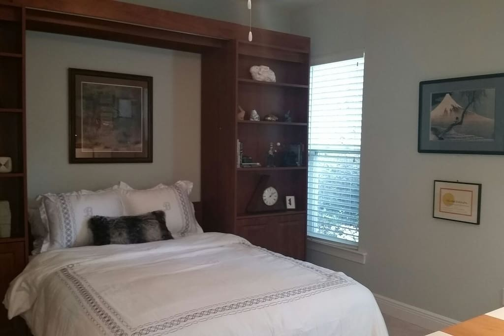 Queen bed with flanking shelves and soft linens. Mt.Fuji on the wall.