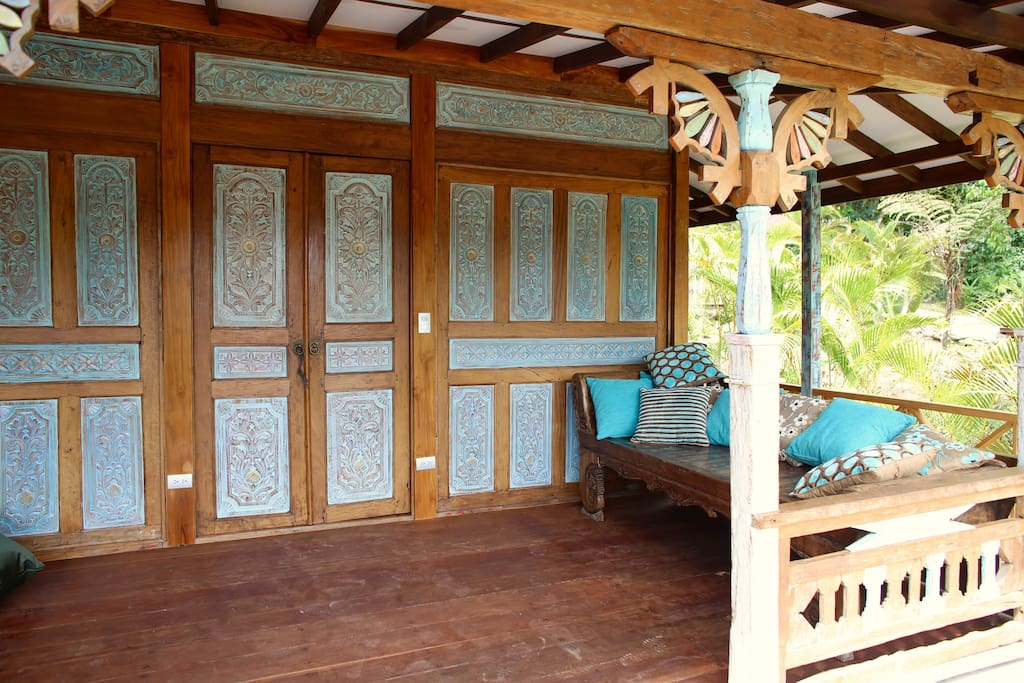 The whole front side of this teak wooden house is wood carved.