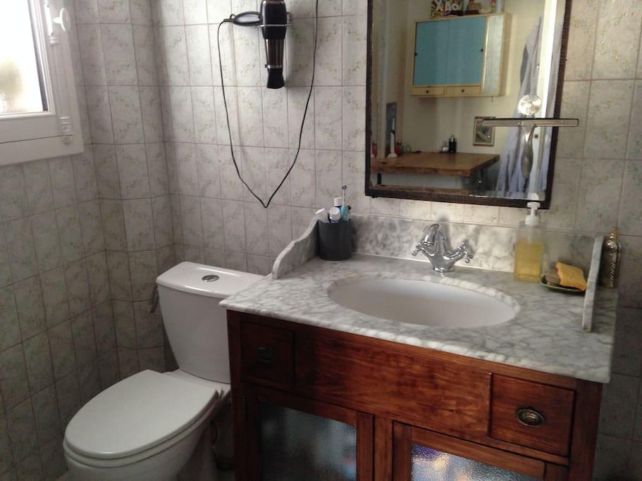 Salle de bain spacieuse avec baignoire, machine à laver linge