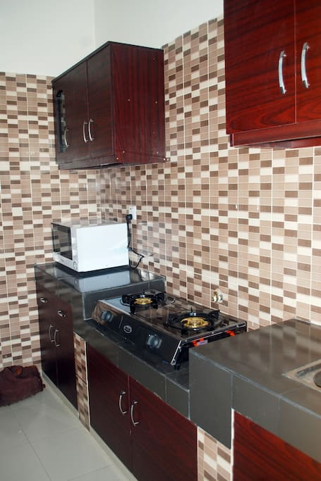 Kitchen with gas cooker, microwave, fridge, sink, store room, and cutlery.