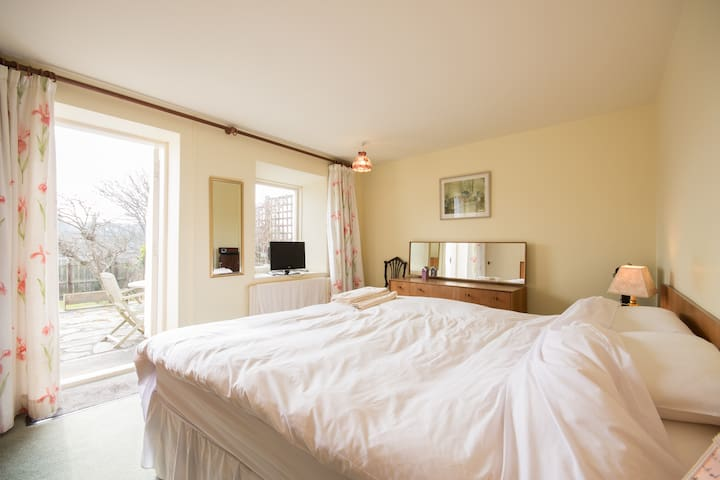 Master bedroom with access to patio and garden. Open the door and listen to the sea.