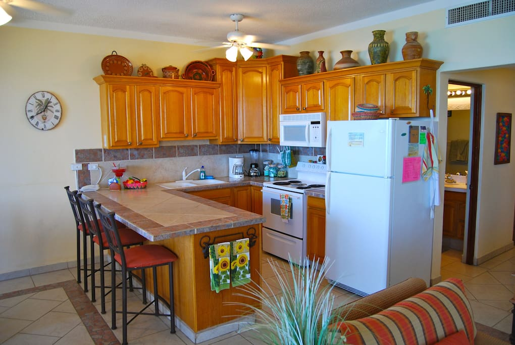 The kitchen has a sitting bar and large counter space.