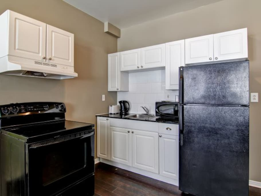 Kitchenette with full fridge and stove.