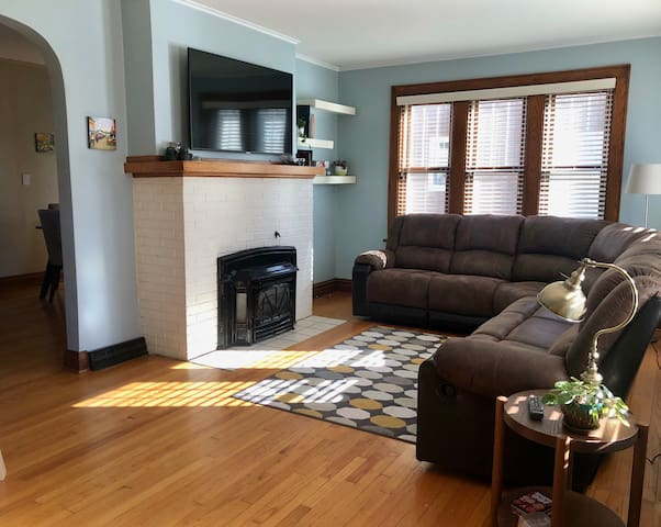 Living room with reclining sofa, smart t.v. and reading lamps.  Fireplace is not operational.