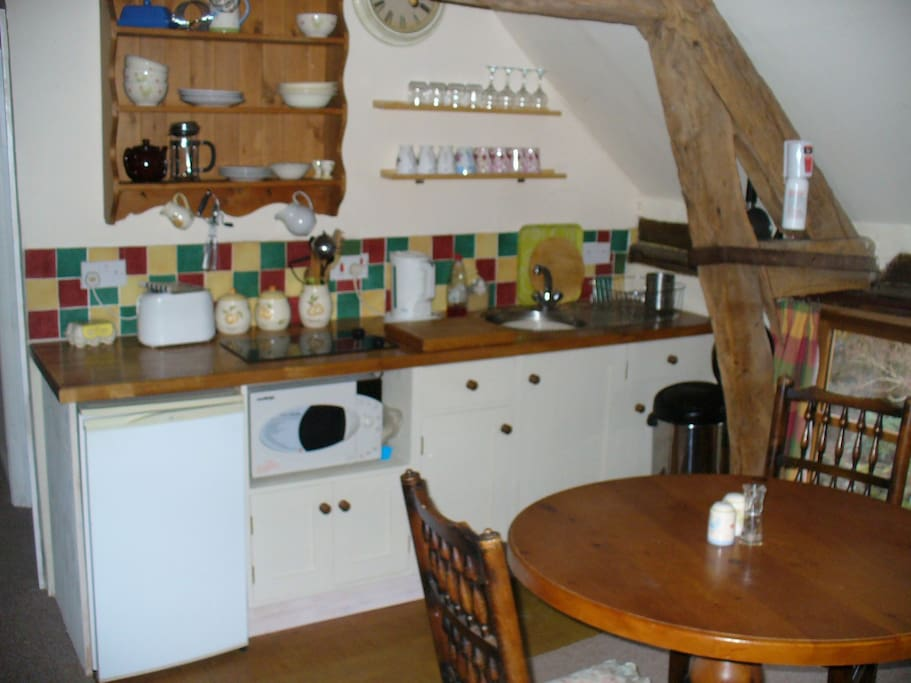 the kitchen with a frudge, hob and combination microwave oven plus a round dining table for your meals