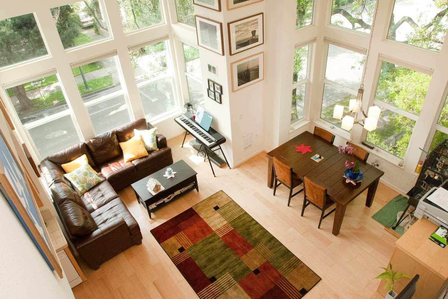 Bird's eye view from condo loft area,  Sofa area with coffee table adjacent to dining area.
