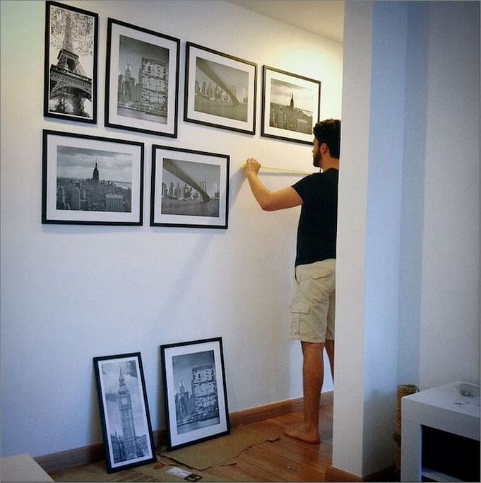The Perfectionist Bastard measuring the walls to hang the frames.