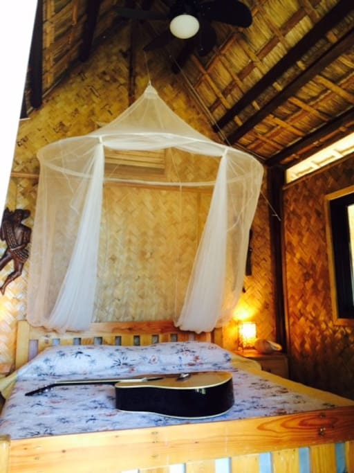 Queen bed, ceiling fan and cool native hut
