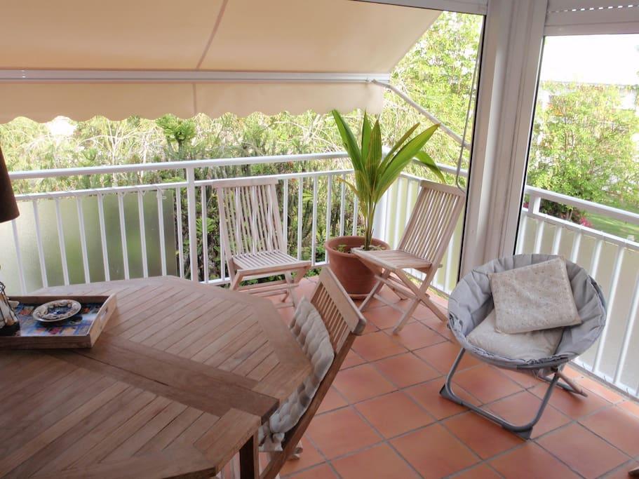 La terrasse-pièce à vivre bien abritée et fermée par volets roulants