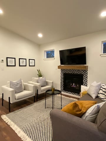 Living room with gas fireplace, sofa bed and lots of morning light!