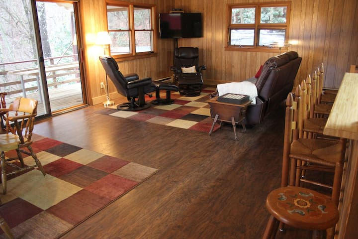 Great room features reclining couch, ergonomic chairs, and flat-screen TV.