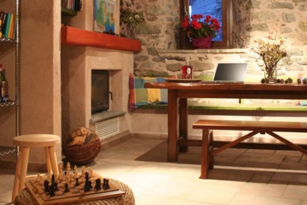 La Crota, la sala comune con camino e possibilità di consultare le cartine o scambiare quattro chiacchiere con gli altri ospiti