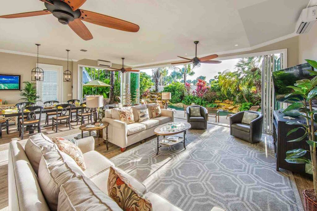 Lovely Key West beach property living room opening up to lush patio