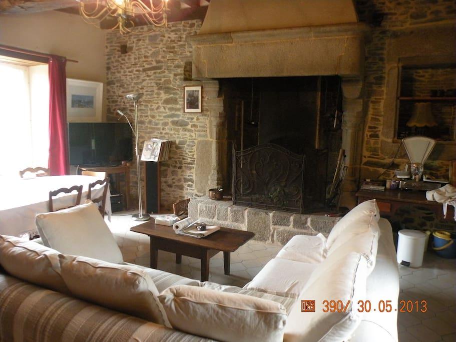Pièce centrale de 30m² avec sa cheminée monumentale du 16èS. Un canapé de 6 places et une SAM de 6 à 8 personnes.