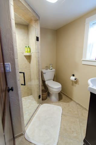 This is probably the biggest tiny bathroom you'll ever see. Walk-in shower (no curb) and adorable vanity sink.