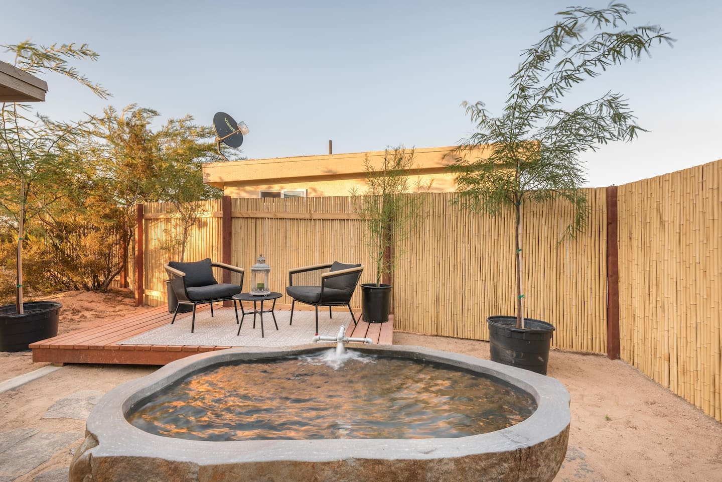 Backyard with private granite stone soaking tub filled with hot mineral springs water.