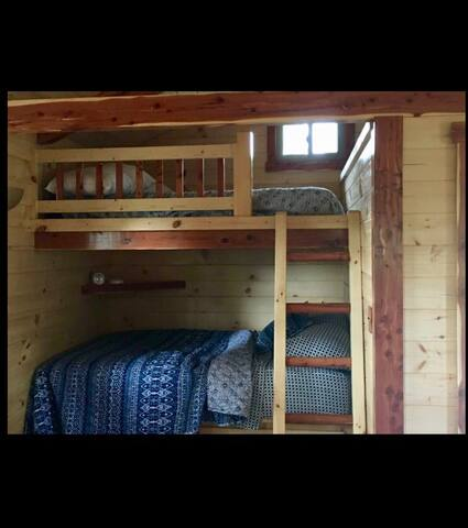 Bunk bed setup. Queen and double. Also, a third single mattress is bunker above the front door. You'll need to use this ladder to access.