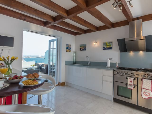 Modern, newly installed kitchen with range cooker. wine cooler, corian worktop...opening onto the seating terrace over the water.