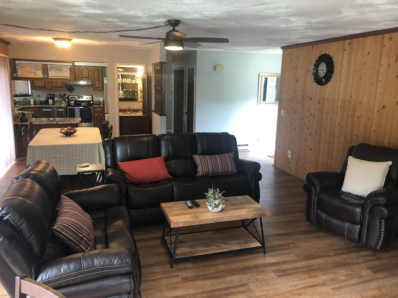 The living room has a new reclining leather sofa set and luxurious wood floors and walls.