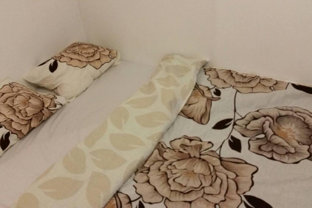 un grand lit avec une bonne qualité de matelas.