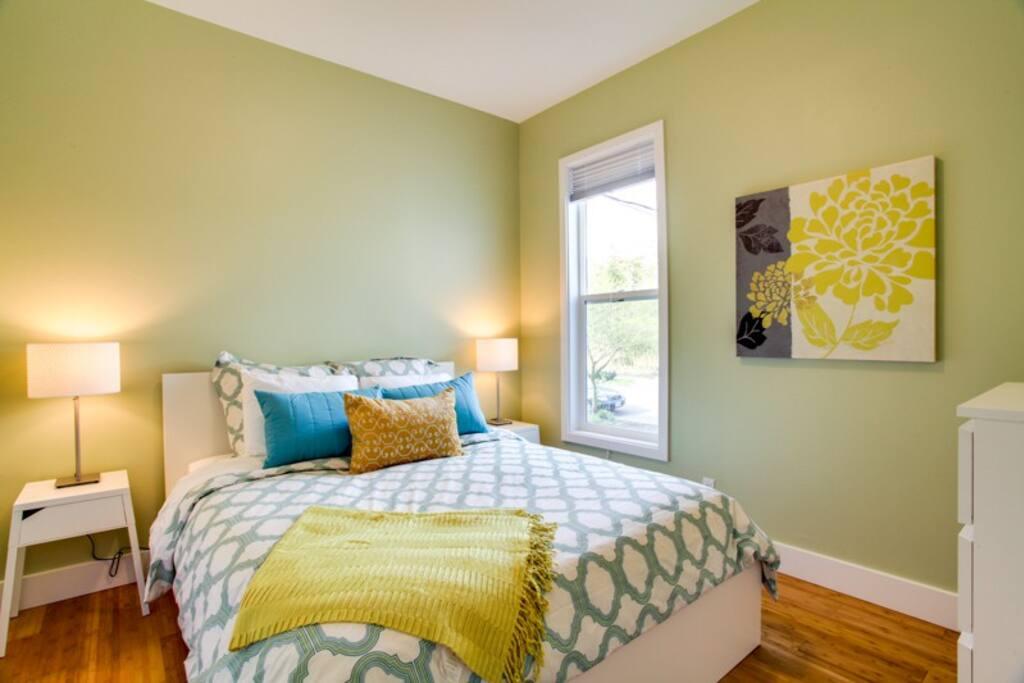 First Bedroom: queen bed, alarm clock, luggage rack, dresser.