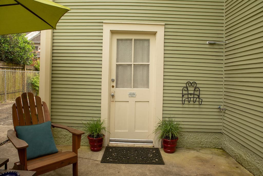 This is your private patio and door to the serene guest suite, located behind wooden fence.